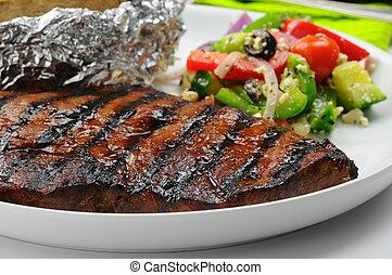 Juicy Steak - Juicy grilled steak served with a greek salad.