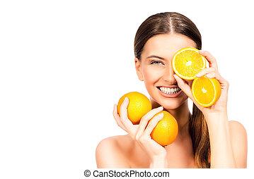 juicy - Joyful young woman holding juicy oranges before her...