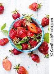 Juicy strawberries in a blue bowl