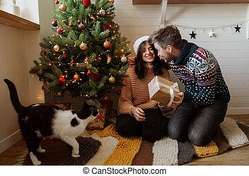 jul., lights., ögonblick, nymodig, jul gåvor, under, holdingen, familj, gåva, träd, room., lycklig, spänd, festlig, utbyte, par, överraskning, munter, ung