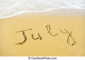 July - written in sand on beach texture - soft wave of the sea