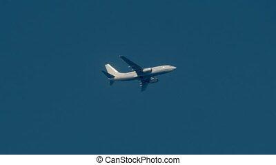 Jumbo jet flying across a prestine blue sky - A windy stormy...