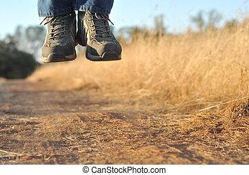 Jump - A person levitating in mid air above a dirt path.
