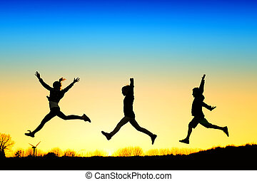 Jump - Active kids jump in meadow at sunset