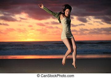 Jump for joy - Happy girl jumps for joy on beach with...
