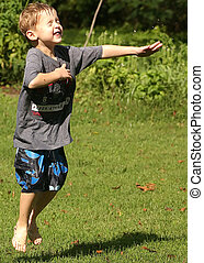 Jump For Summer - A little boy in mid-jump playing in a ...