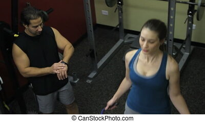 Jump Rope with Trainer - A personal trainer times a woman...