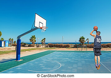 jump shot on the beach - basketball player jump shot in a...