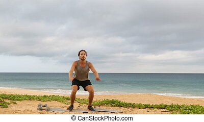 Jump Squats - Man doing Jump Squat exercise workout. Male fitness instructor training on beach. REAL TIME.