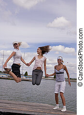 jump with us - three happy and young girls having fun and...