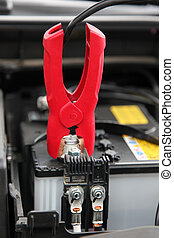 Jumper Cable connected to automobile car battery.