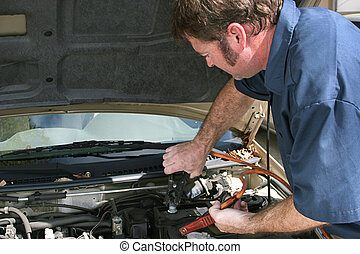 Jumper Cables - An auto mechanic using jumper cables on a...