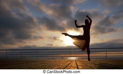 Jumping ballerina in beige dress and pointe on embankment above ocean or sea beach at sunrise.Beautiful blonde woman with long hair practicing stretching and classic exercises.Epic jump.SLOW MOTION.