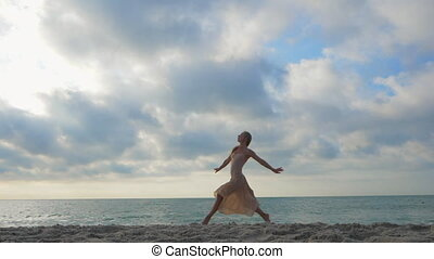 Jumping ballerina in beige silk dress and point on sand beach near sea at sunrise or sunset. Silhouette of young beautiful blonde woman with long hair practicing stretching and classic exercises.