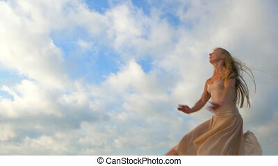 Jumping ballerina in beige silk dress and pointe on sky background. Silhouette of young beautiful blonde woman with long hair practicing stretching and classic exercises. Epic jump. SLOW MOTION.