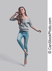 Jumping beauty. Attractive young woman in casual wear...