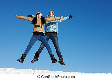 Jumping dates - Portrait of happy couple in warm clothes...