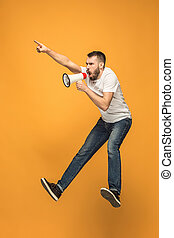 Jumping fan on orange background. The young man as soccer football fan with megaphone