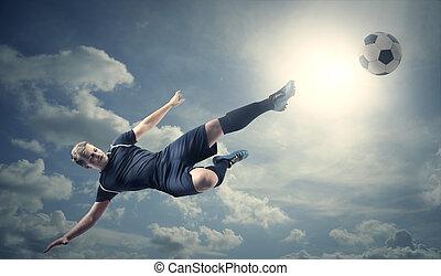 Jumping footballer kicking ball