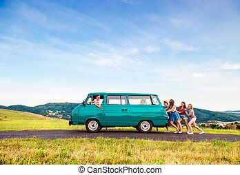 Jumping friends with camper van, green nature and blue sky