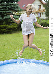 jumping girl - cute blond woman jumping inside a little...