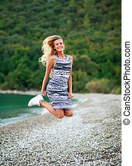 Jumping happy girl on beach on a background of mountains