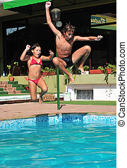 Jumping in pool - Little girl and young boy jumping in pool