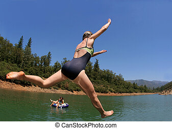 Young woman jumping in the lake