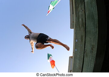 A man jumping off a wharf into the ocean
