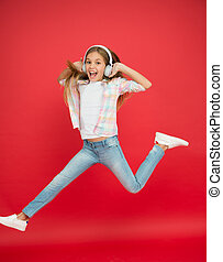 Jumping mid air. Easy listening music. Small girl listening to music in headphones. Dancing girl. Happy small girl dancing. Cute child enjoying happy dance music. Music is happiness for her