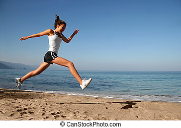 Jumping on the beach - Happy girl running alone on the beach