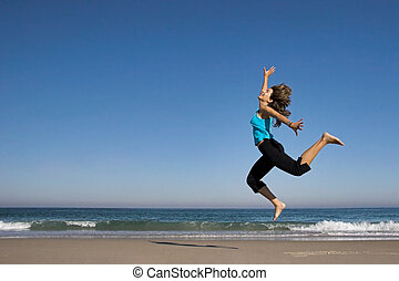 Young active woman jumping on the beach.