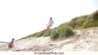 Jumping Over the Sand Dunes - Slow motion, side view, of a...