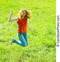 teen girl - Jumping red-haired teen girl against green grass