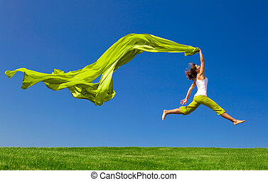 Jumping - Beautiful young woman jumping on a green meadow...