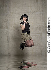 jumping woman - a young woman junping in front of concrete...