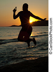 Jumping woman by sunset