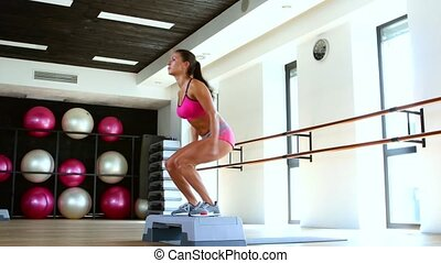 Jumping. Woman doing step jumps at the gym. Dolly shot