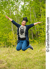Jumping woman in nature