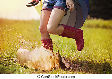 Jumping woman with umbrella and rubber boots