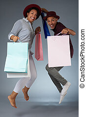 Jumping young couple with shopping bags