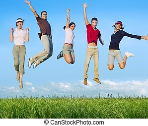 Jumping young people happy group in meadow