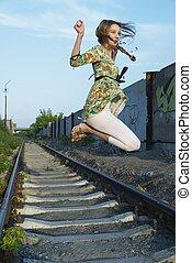 Jumping young woman - Jumping pretty young woman at railway...