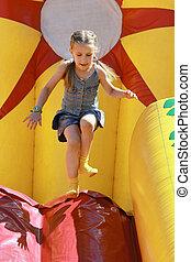 Joyful girl jumps on inflatable attractions