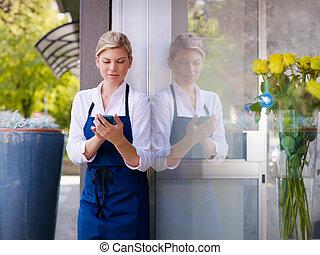 junge frau, arbeitende , als, blumenhändler, in, laden, und, textmessaging