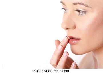 Junge Frau cremt sich ihre Lippen ein