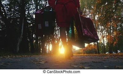 junge frau, in, a, regenmantel, mit, einkaufstüten, geht,...