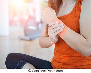 junge frau, massieren, sie, handgelenk, nach, klappend, oder, verletzt, hand, während, nachlässig, sport, üben, mit, tauglichkeitsausrüstung, hintergrund.