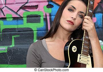 junge frau, mit, gitarre, vor, a, graffiti, wand