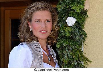 junge Frau neben Tuerkranz - young woman next door wreath